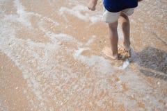 的小男孩走沿海滩的特写镜头后面观点在日落期间 免版税库存图片