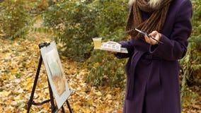 的少女艺术家特写镜头在秋天公园绘在画架的一幅画 免版税库存照片