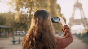 的少妇拍在智能手机的后面观点照片 探索埃佛尔铁塔的少年游人在巴黎,法国 股票视频