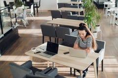 的少妇检查在她的smartwatch的顶上的观点时间,当研究她的膝上型计算机在咖啡馆时 顶视图被射击  免版税库存照片