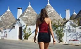 的少妇选择trullo的后面观点 看阿尔贝罗贝洛trulli的屋顶在旅行的女孩在南意大利 免版税库存照片