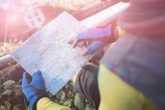 的山骑自行车的人看地图的大角度观点 库存图片