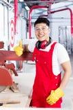 他的工作场所的骄傲的工作者在工厂设备 图库摄影