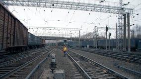 的工作者橙色总体和一件盔甲在铁路轨道附近 许多火车在背景中 股票录像