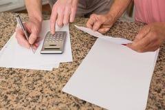 付他们的帐单的资深夫妇 免版税库存照片