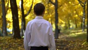 的年轻人白色shirtwalks在秋天公园 影视素材