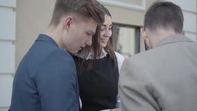 的年轻女人和谈论两个的人礼服的文件在大阳台 业务关系 概念的自由职业者 影视素材