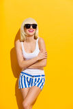 的微笑的白肤金发的女孩有横渡的胳膊的太阳镜 免版税库存图片