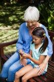 的微笑的祖母看孙女的大角度观点使用在长木凳的手机 免版税库存照片