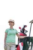 的微笑的高尔夫球运动员站立反对清楚的天空的低角度观点 库存图片