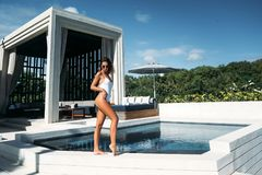 的性感的女孩放松在与海洋的游泳池的惊人的观点在背景 白色比基尼泳装的可爱的少妇 免版税库存照片
