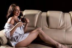 的性感的妇女白人坐一个皮革沙发和拿着咖啡的衬衣在黑暗的背景 免版税图库摄影