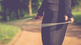 的手特写镜头跳绳的跳跃的妇女 户外运动 跳在公园道路的一条跨越横线的女孩有一绿色gra的 影视素材