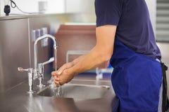 洗他的手的厨房搬运工 免版税图库摄影