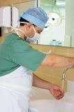 洗他的手的外科医生在手术室 库存图片