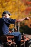 他的拖拉机的一位农夫在秋天在新罕布什尔 库存照片