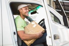 他的拿着小包的搬运车的微笑的交付司机 免版税库存照片
