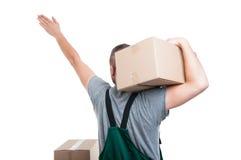 的搬家工人人拿着箱子的后面观点显示方向 免版税库存图片