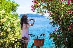 的旅游妇女拍与电话的后面观点照片 库存照片