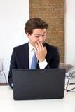 读他的有偷笑的商人膝上型计算机 库存照片