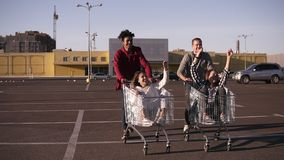 的正面图年轻朋友的获得乐趣户外在购物台车 赛跑在购物的不同种族的年轻人 股票视频