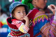 他的母亲后面的一个小Hmong (苗族)孩子 库存照片