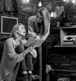 的母亲和一起读的女儿或者的姐妹,家庭娱乐活动 笑关于在书的滑稽的场面的女孩 免版税库存照片