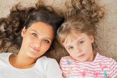 的母亲和一起说谎小的女儿 库存图片