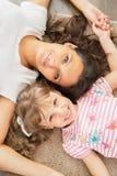 的母亲和一起说谎小的女儿 免版税库存照片