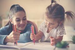 的母亲和在家写愉快的女孩一起使用和 库存照片