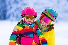 的母亲和学会的小女孩滑雪 免版税库存图片