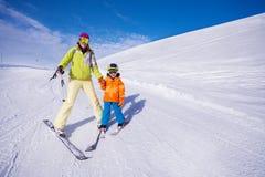 的母亲和学会的小男孩滑雪握手 免版税库存照片