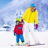 的母亲和学会的小男孩滑雪 免版税库存图片