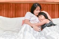 的母亲和拥抱她的女儿,当睡觉时 免版税库存图片