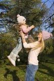 的母亲和获得她的小女孩乐趣 图库摄影