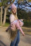 的母亲和获得她的小女孩乐趣 免版税库存照片