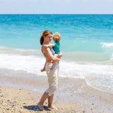 的母亲和获得小小孩的男孩在海滩的乐趣 库存图片