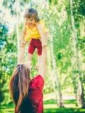 的母亲和获得他的小的女儿乐趣 库存照片