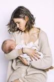 他的母亲的胳膊的一个孩子 妈妈打扮时兴地 丝绸球衣 免版税库存图片