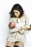 他的母亲的胳膊的一个孩子 妈妈打扮时兴地 丝绸球衣 库存照片