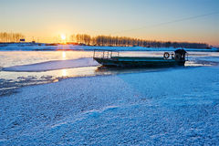 冻结的河和小船日落 免版税库存图片
