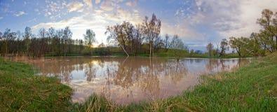 洪水的河在日落 免版税库存图片