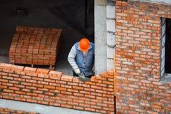 的泥工放置砖的观点在工地工作 免版税图库摄影
