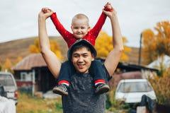 的父亲和使用他的小的儿子户外 小男孩坐他的父亲肩膀 免版税库存图片