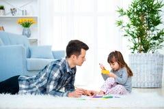 的父亲和有一点的女儿质量家庭时间一起在家 有说谎在与五颜六色的温暖的地板图画的女孩的爸爸 库存图片