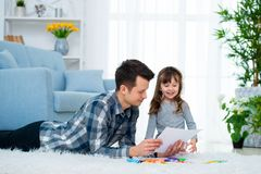 的父亲和有一点的女儿质量家庭时间一起在家 有说谎在与五颜六色的温暖的地板图画的女孩的爸爸 免版税库存照片