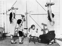 的父亲和有他的三个的孩子与哑铃的一种锻炼(所有人被描述不更长生存,并且庄园不存在 S 免版税图库摄影