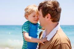 的父亲和获得小小孩的男孩在海滩的乐趣 免版税库存图片