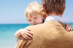 的父亲和获得小小孩的男孩在海滩的乐趣 图库摄影
