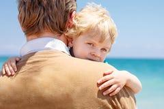 的父亲和获得小小孩的男孩在海滩的乐趣 免版税库存照片